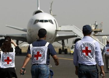 Members of the International Committee of the Red Cross walk towards a plane loaded with Emergency medical