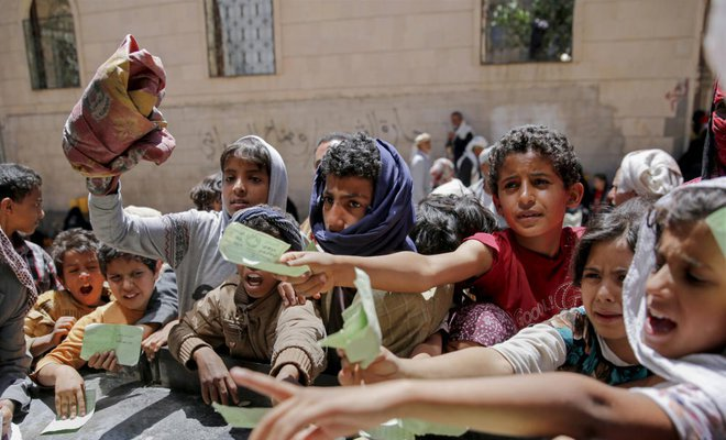 Yemeni children present documents in order to receive food rations provided by a local charity, in Sanaa, Yemen. (AP)