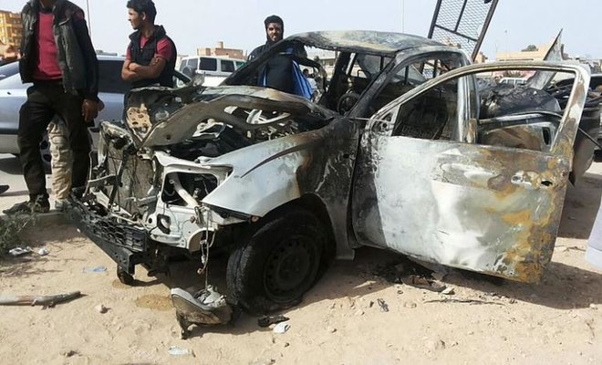 In this file photo, people stand at the scene of a car bomb explosion in Libya. (Reuters)