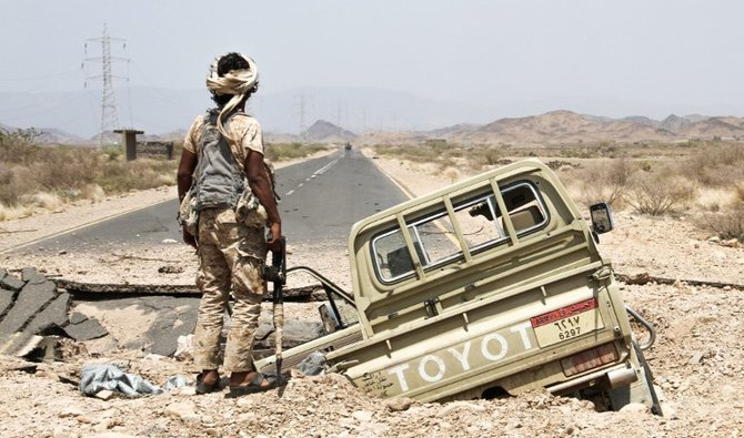 A Yemeni fighter loyal to the Saudi-backed Yemeni president stands next to an army Toyota pickup truck as it lies in hole on the road leading to Khaled Ibn Al-Walid base, 30 kilometres (20 miles) east of the government-held Red Sea port town of Mokha, on April 15, 2017. The Khaled Ibn Al-Walid camp, one of the biggest in Yemen, sits on a key road linking Mokha to the Huthi-controlled port city of Hodeida and third city Taez, which is under rebel siege. Loyalist forces launched a major offensive on January 7 to retake Yemen's 450-kilometre (280-mile) coastline as far as Midi, close to the Saudi border. / AFP PHOTO / SALEH AL-OBEIDI