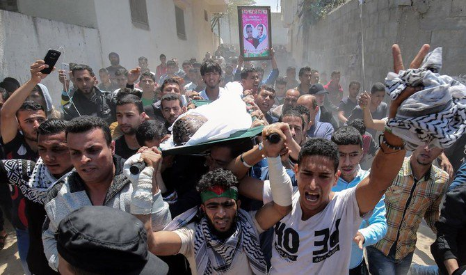 Mourners carry the body of Palestinian Tahrir Wahada, 18, during his funeral in Khan Yunis, in the southern Gaza Strip April 23, 2018. /AFP