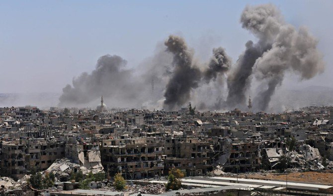 A picture taken during a government guided tour shows smoke rising from buildings in Yarmuk, a Palestinian refugee camp on the edge of Damascus, during regime shelling targeting Daesh group positions on April 24. (AFP)