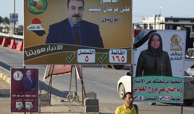 A man walks past posters of candidates for legislative elections in Ramadi, Anbar province. Parliamentary elections next month are an opportunity for the predominantly Sunni residents to settle scores. (AFP)