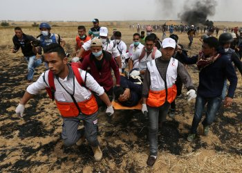 A wounded Palestinian is evacuated during clashes with Israeli troops at a protest where Palestinians demand the right to return to their homeland, at the Israel-Gaza border in the southern Gaza Strip, April 20, 2018. REUTERS/Ibraheem Abu Mustafa