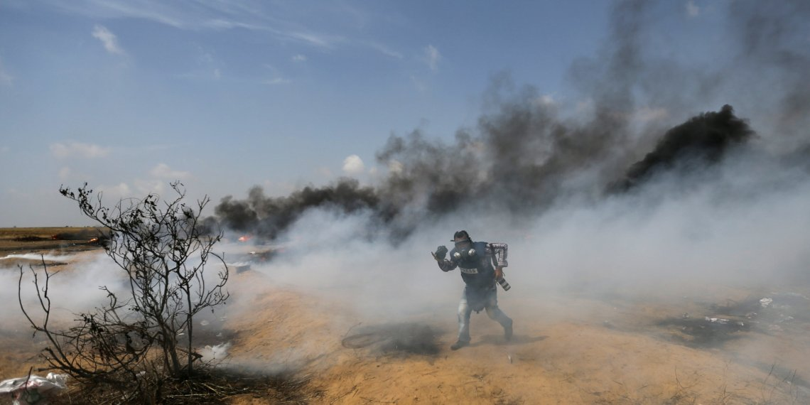 A photojournalist runs during clashes between Israeli troops and Palestinians at a protest where Palestinians demand the right to return to their homeland, at the Israel-Gaza border in the southern Gaza Strip, April 27, 2018. REUTERS/Ibraheem Abu Mustafa
