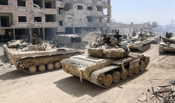 A picture taken on April 8, 2018, shows Syrian Army soldiers gathering in an area on the eastern outskirts of Douma, as they continue their fierce offensive to retake the last opposition holdout in Eastern Ghouta. The Syrian government unleashed a ferocious assault on the then-rebel stronghold of Eastern Ghouta on February 18, aiming to crush Islamist and jihadist groups on the doorstep of the capital. / AFP PHOTO / STRINGER