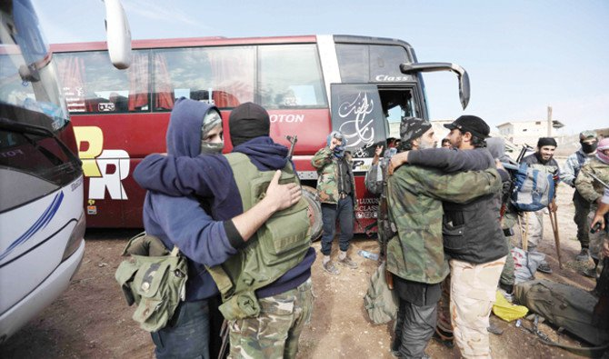 Fighters from Hayat Tahrir Al-Sham arrive with their family members in a rebel-held area of the Al-Eis crossing in Syria's northern Aleppo province after they were evacuated from the Palestinian refugee camp of Yarmouk on Tuesday. (AFP)