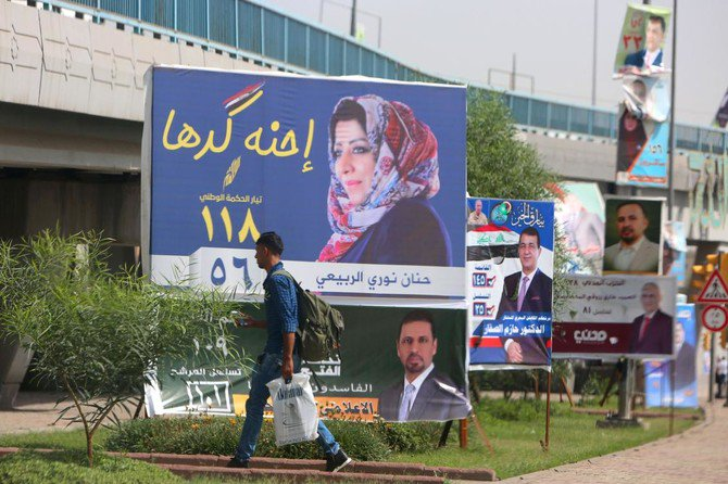 "A man walks past electoral campaign posters in Baghdad on May 8, 2018. Arabic slogan on Hanan Nouri al-Rubaye's billboard (C) reads: ""We are up to it"". With campaign posters cluttering the streets of Iraq, the almost 7,000 candidates running for parliament in upcoming elections are resorting to increasingly wacky pitches to woo voters. / AFP / SABAH ARAR"