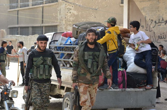 """Syrian opposition fighters and their families prepare to leave the town of Yalda on the outskirts of Damascus on May 4, 2018, under a negotiated withdrawal to secure the last opposition holdouts of the capital. The evacuees are heading to opposition-held parts of northern Syria. Beit Saham, Yalda, and Babila had for several years fallen under a """"reconciliation"""" agreement with the Syrian state, meaning they remained in rebel hands but a local ceasefire was enforced. But after capturing the Eastern Ghouta rebel stronghold outside Damascus last month, regime forces have sought to secure the entirety of the capital and its surroundings with a blend of military operations and negotiated withdrawals  / AFP / Rami al SAYED"""