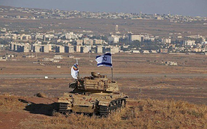 An Israeli flag flutters above the wreckage of a tank on a hill in the Golan Heights overlooking the border with Syria. The strategic plateau has long been disputed by Syria and Israel. (AFP)