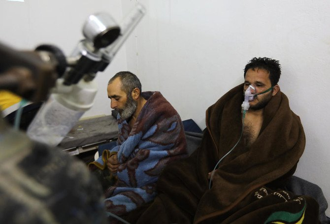 Syrians suffering from breathing difficulties following Syrian regime air strikes on the northwestern town of Saraqeb rest around a stove at a field hospital in a village on the outskirts of Saraqeb (Omar Hajj Kadour/AFP)