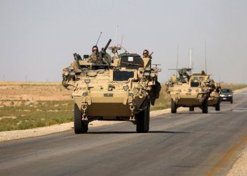 US troops sit atop an armoured vehicle on a road near the northern Syrian village of Ain Issa. (AFP)