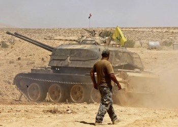 A fighter walks past a tank bearing a Hezbollah flag in the Qara area, in Syria's Qalamoun region, on August 28, 2017. (Louai Beshara/AFP)