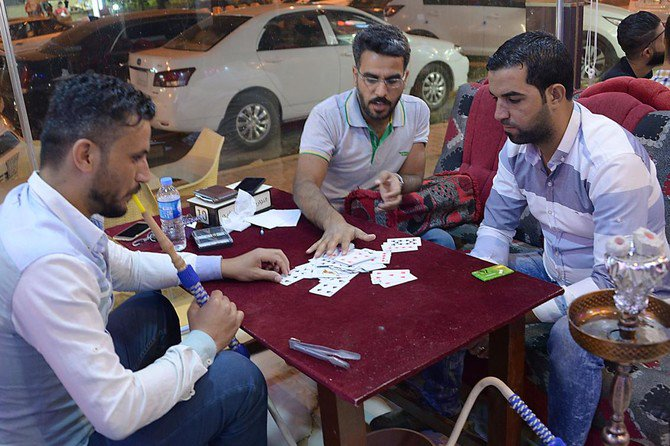 Men play cards after breaking the fast during the holy month of Ramadan in Mosul. Most of Mosul's restaurants and open-air cafes closed their doors after Daesh controlled the city. (AFP)