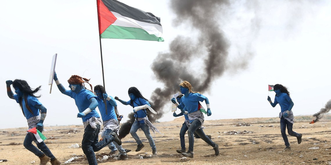 Palestinians with their faces painted like characters from the movie Avatar take part in a protest demanding the right to return to their homeland, at the Israel-Gaza border in the southern Gaza Strip. REUTERS/Ibraheem Abu Mustafa