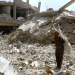 FILE PHOTO: A woman gestures as she stands on rubble of damaged buildings in Raqqa, Syria May 14, 2018. REUTERS/Aboud Hamam/File Photo
