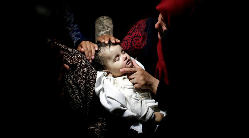 A relative mourns as she carries the body of eight-month-old Palestinian infant Laila al-Ghandour, who died after inhaling tear gas during a protest against U.S embassy move to Jerusalem at the Israel-Gaza border, during her funeral in Gaza City May 15, 2018. (REUTERS)