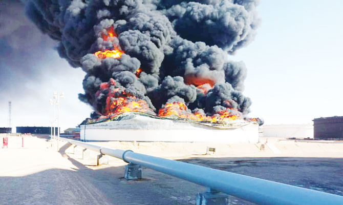 Smoke and flames rise from an oil storage tank that was set on fire amid fighting between rival factions at Ras Lanuf terminal, Libya. /Reuters