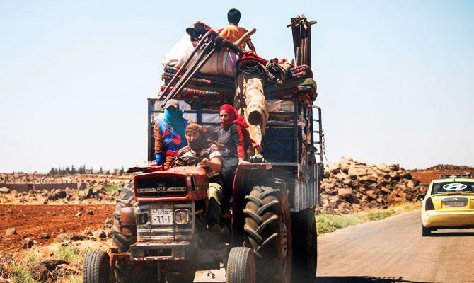 A Syrian family rides with belongings on a tractor-drawn trailer as they flee from fighting in the southern Syrian province of Daraa on June 21, 2018. (AFP)