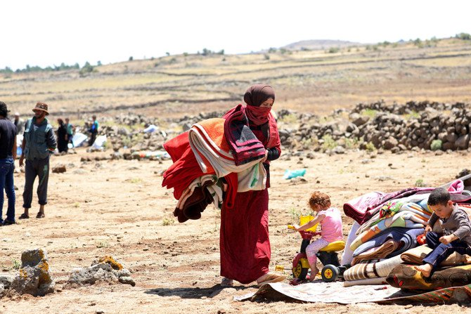 An internally displaced woman from Deraa province in Syria holds blankets near the Israeli-occupied Golan Heights. The poll ranked Syria second worst behind Afghanistan for the risks women faced from non-sexual violence and for access to health care. /(Reuters)