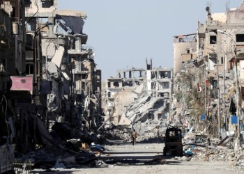FILE PHOTO: A fighter of Syrian Democratic Forces stands amidst the ruins of buildings near the Clock Square in Raqqa, Syria October 18, 2017.  REUTERS/Erik De Castro/File photo