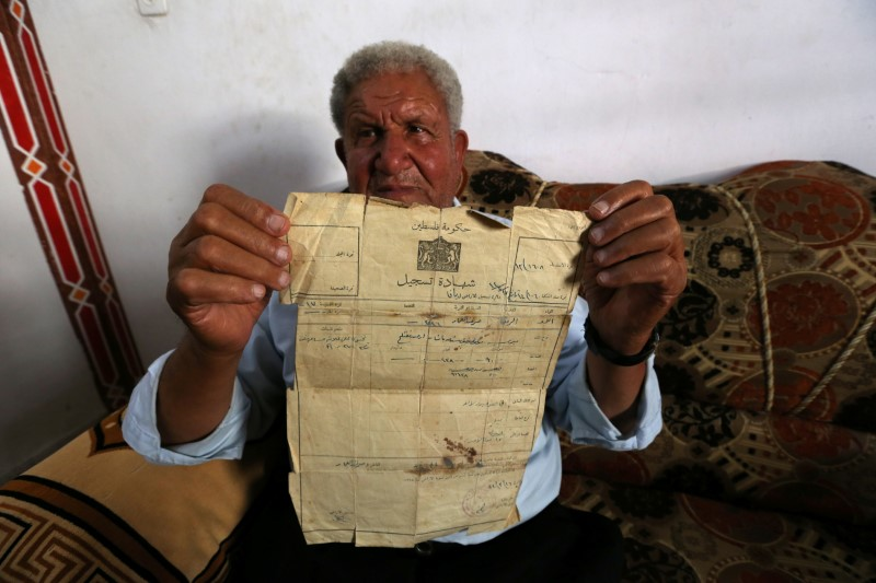 Palestinian Ahmed Jarghoun, 75, displays a land registration certificate from the British era, in Khan Younis in the southern Gaza Strip June 18, 2018. Picture taken June 18, 2018. REUTERS/Ibraheem Abu Mustafa