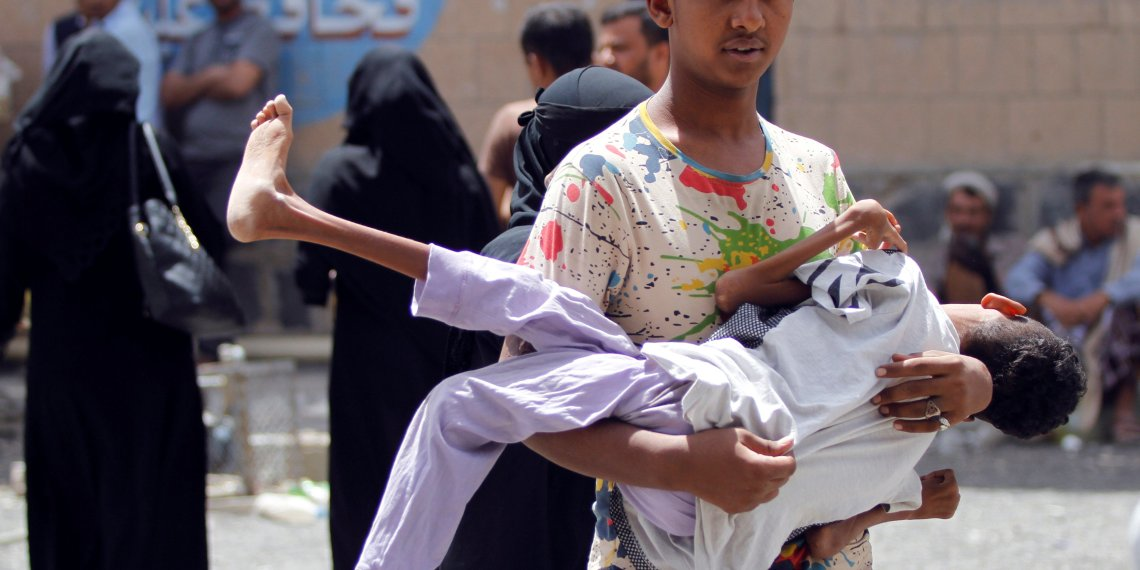 A displaced boy from Hodeidah city carries his brother who is affected by monoplegia, at a school where displaced people live, in Sanaa, Yemen June 22, 2018. REUTERS/Mohamed al-Sayaghi
