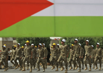 "Fighters of paramilitary units walk past a big Palestinian flag during a rally to mark ""Quds day"" in Baghdad on Friday, June 8, 2018. (AFP)"