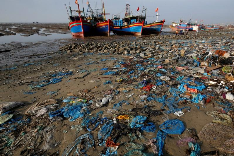 FILE PHOTO: Fishing boats are seen on a beach covered with plastic waste in Thanh Hoa province, Vietnam June 4, 2018. REUTERS/Nguyen Huy Kham/File Photo