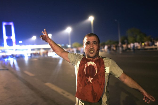 A man covered with blood points at the Bosphorus bridge as Turkish military clashed with people at the entrance to the bridge in Istanbul on July 16, 2016. (Bulent Kilic/AFP)