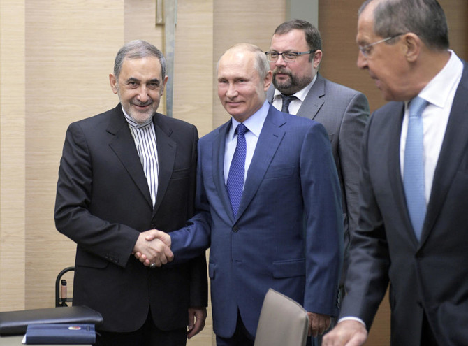 Russian President Vladimir Putin, center, shakes hands with Ali Akbar Velayati, a senior adviser to Iran's Supreme Leader Ayatollah Ali Khamenei. (Alexei Druzhinin, Sputnik, Kremlin Pool Photo via AP)