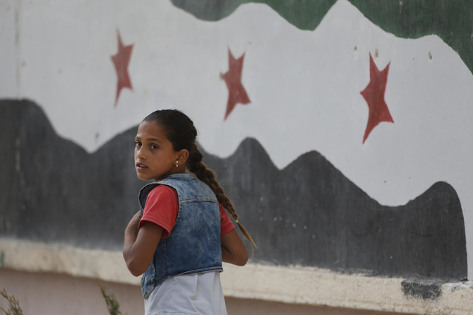 In this Wednesday, May 30, 2018, photo, a Syrian girl walks past a hospital in Jarablus, northern Syria. (AP/Lefteris Pitarakis)
