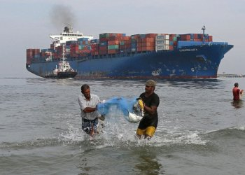 Fishermen carry bluefin trevally fish locally known as Vatta as a cargo ship carrying containers moves in the Arabian Sea in Kochi, India, May 9, 2018. (File Photo: Sivaram V/Reuters)