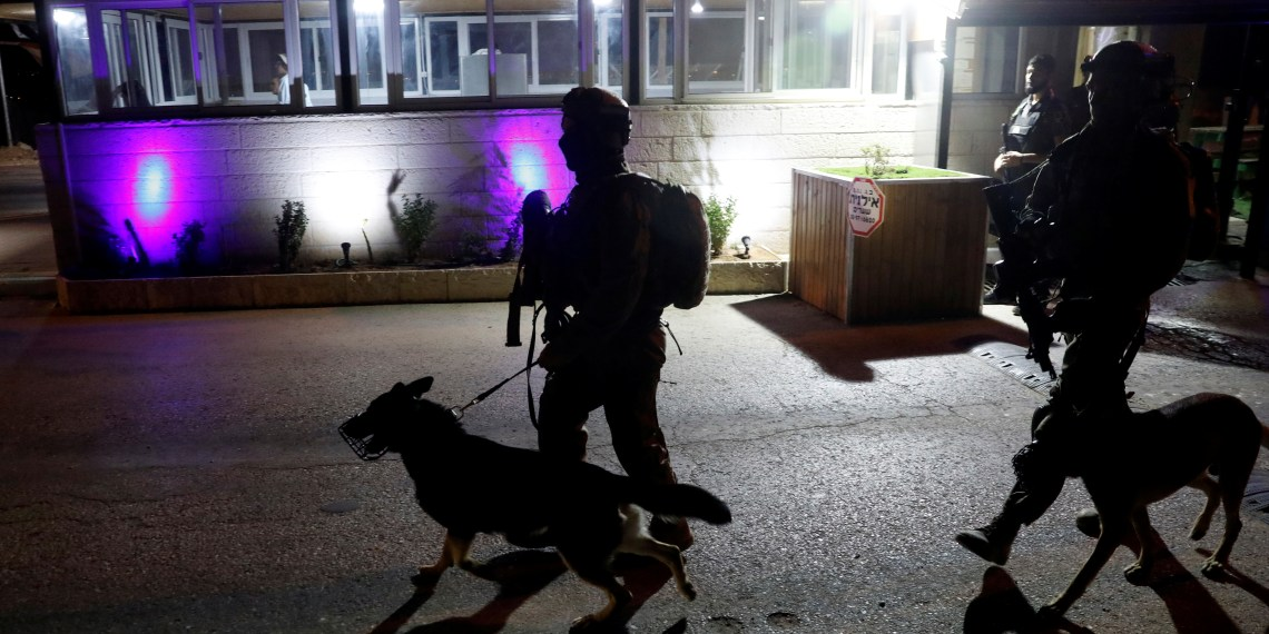 Israeli soldiers patrol with their dogs near the entrance of Israeli settlement Adam after a Palestinian assailant stabbed three people and then was shot and killed, according to the Israeli military, in the occupied West Bank, July 26, 2018 REUTERS/Ronen Zvulun