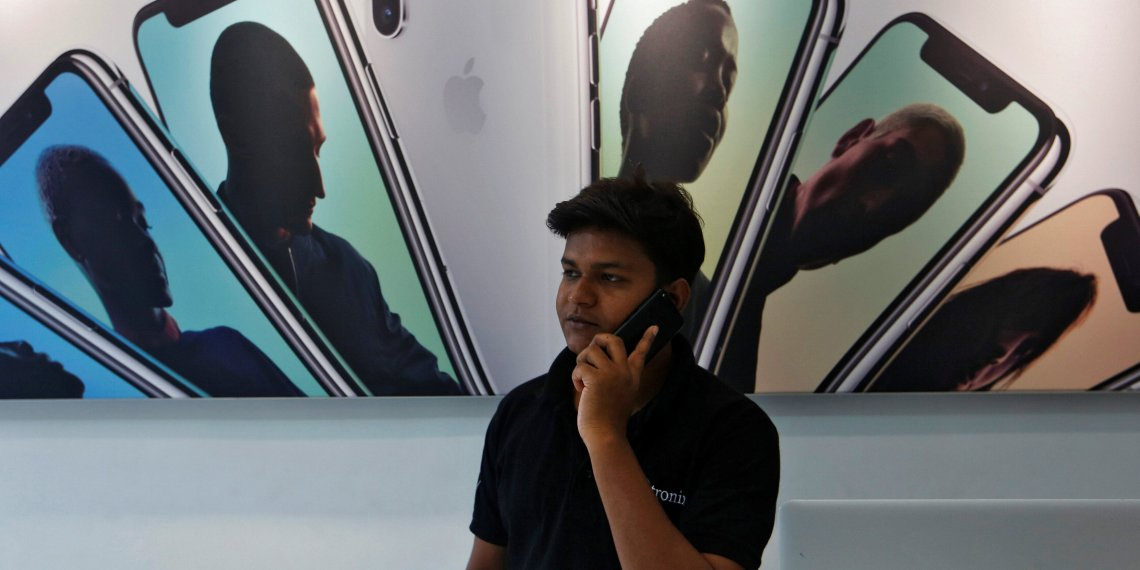 FILE PHOTO: A salesperson speaks on the phone at an Apple reseller store in Mumbai, India July 27, 2018. REUTERS/Francis Mascarenhas