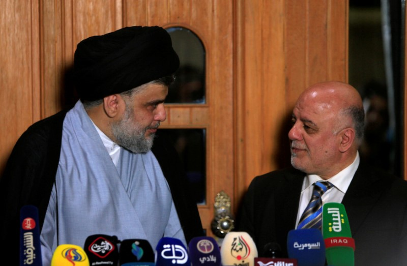 Iraqi Shi'ite cleric Moqtada al-Sadr, who's bloc came first, looks at Iraqi Prime Minister Haider al-Abadi, who's political bloc came third in a May parliamentary election, during a news conference in Najaf, Iraq June 23, 2018. REUTERS/Alaa al-Marjani
