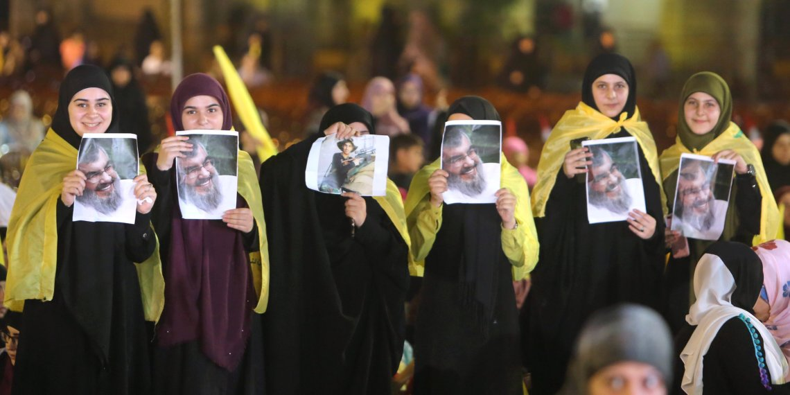 Female supporters display a picture of Lebanon's Hezbollah leader Sayyed Hassan Nasrallah as he makes an address via a screen in Beirut, Lebanon August 14, 2018. REUTERS/Aziz Taher