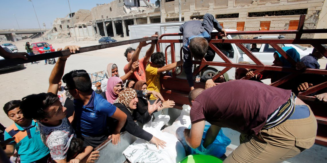 Citizens gather around a car that distribute meat for the poor families in the old city of Mosul, Iraq August 22, 2018. REUTERS/Khalid al-Mousily