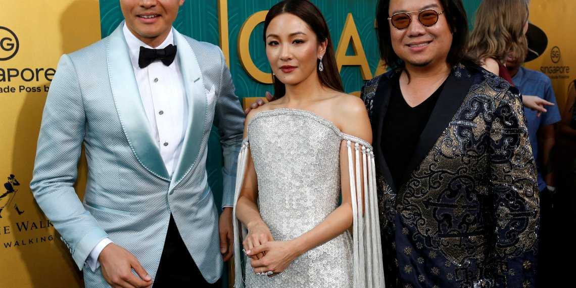 "FILE PHOTO: Author Kevin Kwan (R) and cast members Henry Golding and Constance Wu pose at the premiere for ""Crazy Rich Asians"" in Los Angeles, California, U.S., August 7, 2018. REUTERS/Mario Anzuoni/File Photo"