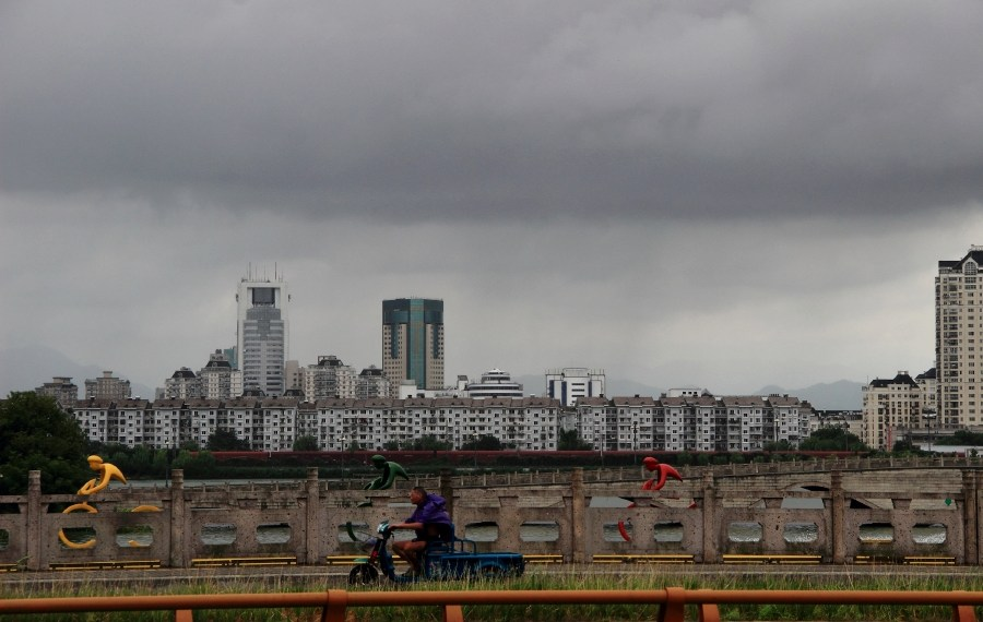 A man rides a vehicle as dark clouds gather above the city of Shaoxing before Typhoon Yagi is expected to make landfall in Zhejiang province, China August 12, 2018. REUTERS/Stringer  ATTENTION EDITORS - THIS IMAGE WAS PROVIDED BY A THIRD PARTY. CHINA OUT.