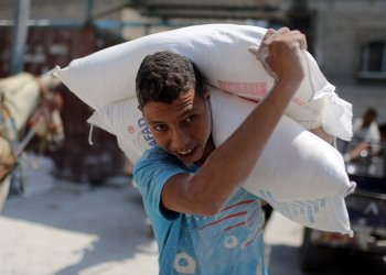 A Palestinian carries bags of flour at an aid distribution center run by the United Nations Relief and Works Agency (UNRWA), in Khan Younis in the southern Gaza Strip September 3, 2018. REUTERS/Ibraheem Abu Mustafa