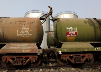 FILE PHOTO: A worker walks atop a tanker wagon to check the freight level at an oil terminal on the outskirts of Kolkata, India November 27, 2013. REUTERS/Rupak De Chowdhuri/File Photo