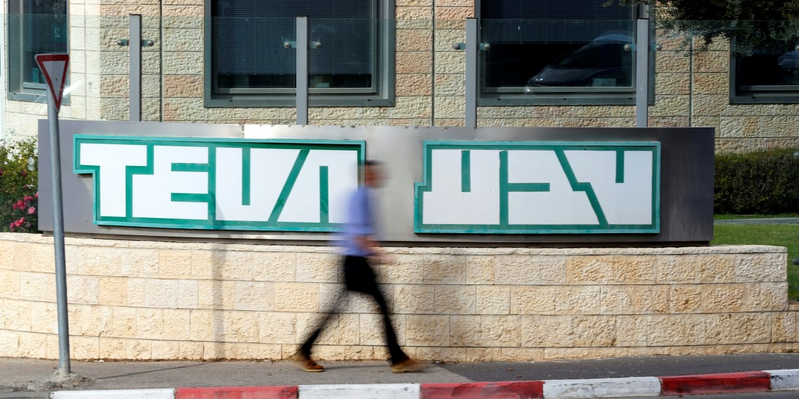 A man walks past the logo of Teva Pharmaceutical Industries at their plant in Jerusalem December 14, 2017. REUTERS/Ammar Awad