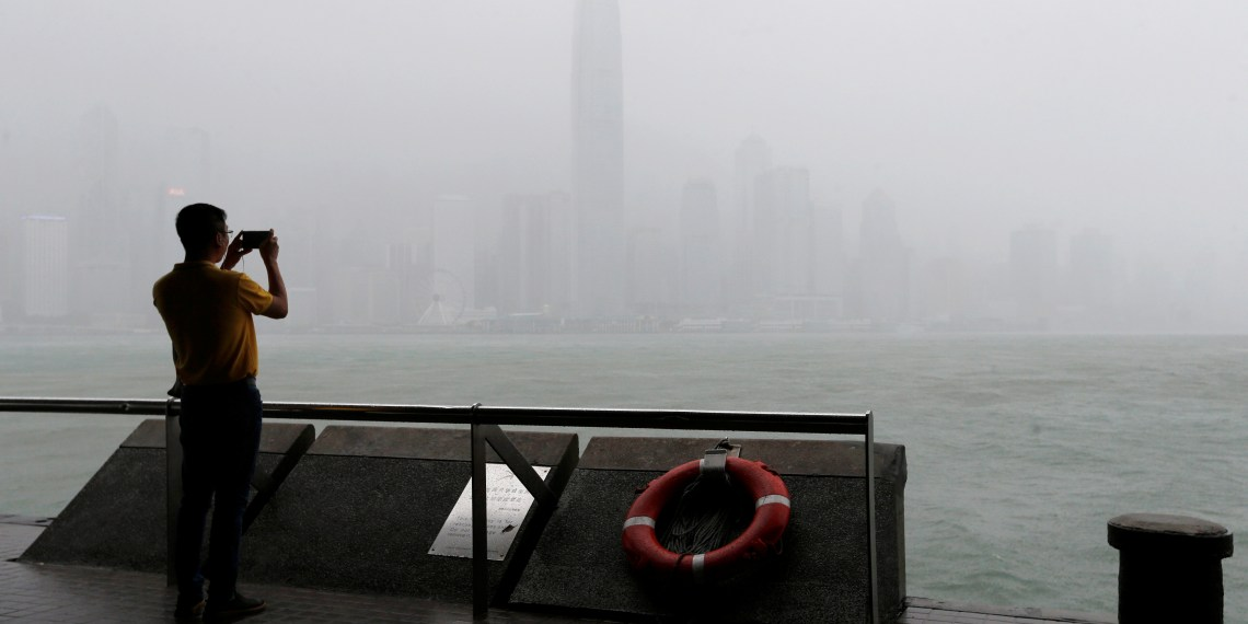 A man takes a photo on the waterfront while heavy rains fall on Victoria Harbour as Typhoon Mangkhut approaches Hong Kong, China September 16, 2018. REUTRERS/Bobby Yip
