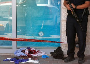 Blood-stained clothes and a bullet hole in a glass panel are seen at the scene of a stabbing attack near a mall in the Gush Etzion Junction in the occupied West Bank, September 16, 2018. REUTERS/Ronen Zvulun