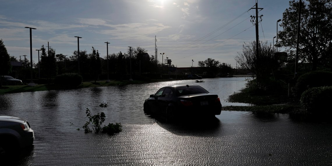 The sun reflects on flood water and stranded vehicles as it emerges after days of storm clouds and rain, in the aftermath of Hurricane Florence in Wilmington, North Carolina, U.S., September 17, 2018. REUTERS/Jonathan Drake