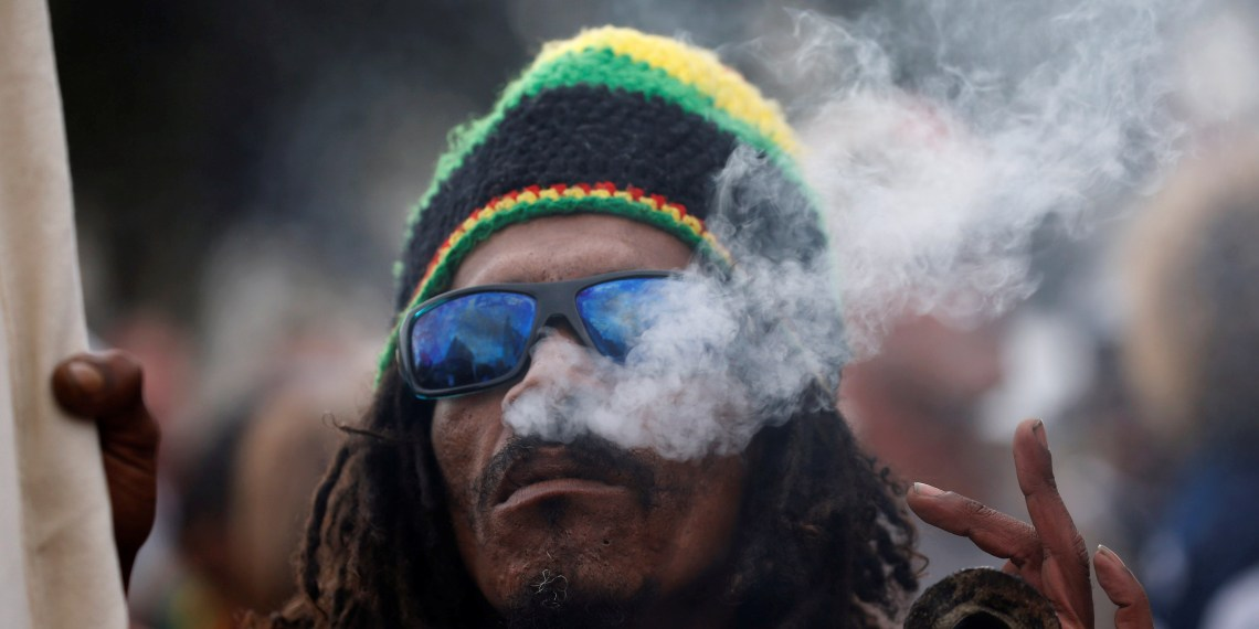 A man smokes marijuana, known locally as dagga, during a march calling for the legalisation of cannabis in Cape Town, South Africa, May 6, 2017. REUTERS/Mike Hutchings