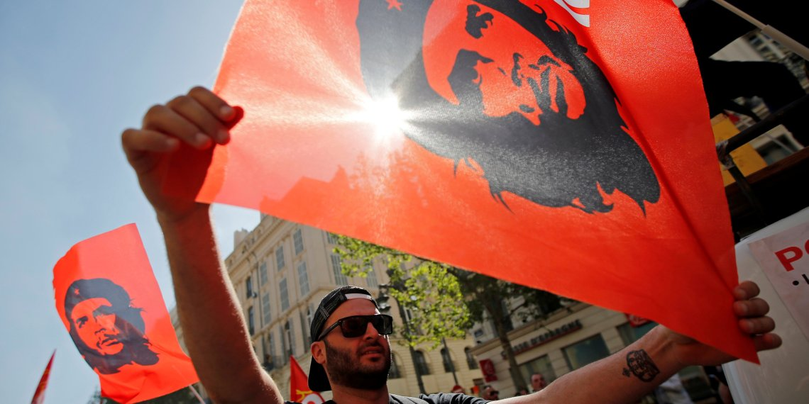 """FILE PHOTO: Workers wave CGT labour union flags with an image of revolutionary hero Ernesto """"Che"""" Guevara during a demonstration against the French government's reform plans in Marseille as part of a national day of protest, France, April 19, 2018. REUTERS/Jean-Paul Pelissier/File Photo"""