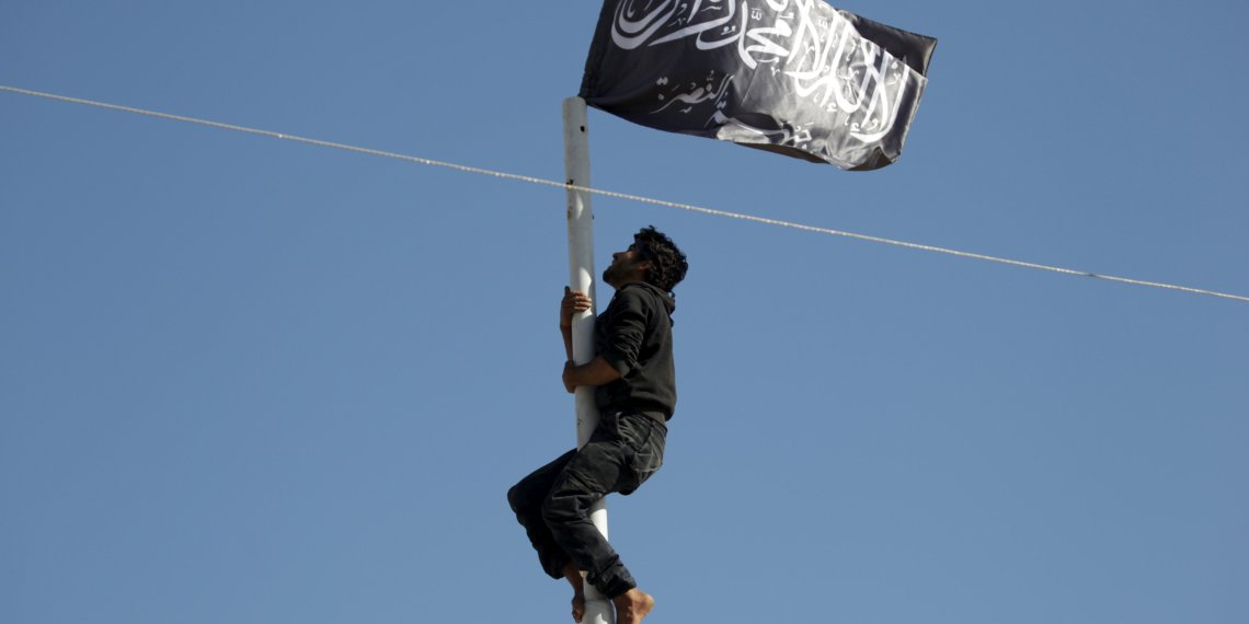 FILE PHOTO: A member of Nusra Front climbs a pole where a Nusra flag waves in the town of Ariha in Syria's Idlib province, May 29, 2015.  REUTERS/Khalil Ashawi