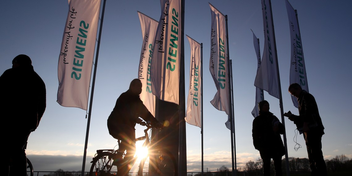 FILE PHOTO: People pass Siemens flags ahead of the company's annual shareholders meeting in Munich, Germany, January 31, 2018. REUTERS/Michael Dalder